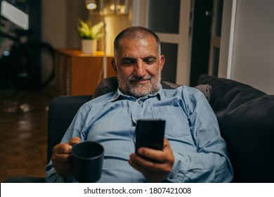 middle aged man sitting sofa using mobile phone at home