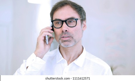 Middle Aged Man Talking on Phone, Attending Phone Call