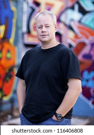 Middle aged man with urban graffiti background