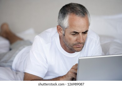 Middle aged man using laptop while lying in bed