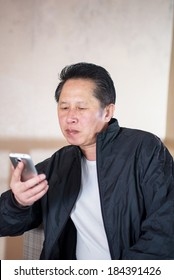 Middle aged Man View Smartphone in the cafe