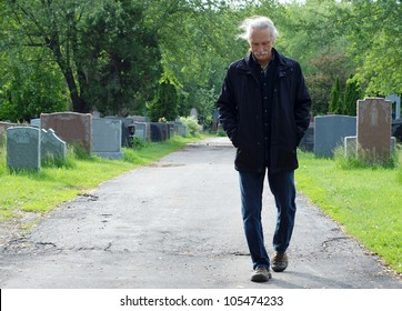 Middle aged man walking in cemetery with head down.