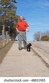A middle aged man walking his dog on the first warm day in spring.
