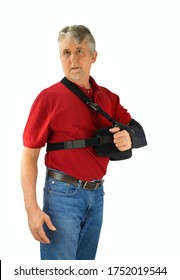 Middle aged man wearing a shoulder surgery sling with abduction pillow to keep his arm in the proper position during recovery and healing after his operation.