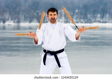 The middle aged man in white kimono and black belt is practicing martial arts with two wooden nunchaku at winter.