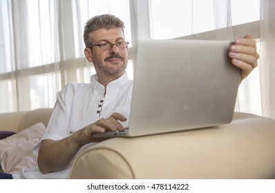 middle aged man working in his computer at home