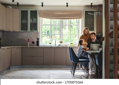 Middle aged man working on laptop computer in domestic kitchen surrounded by cute little daughter drinking juice and beautiful loving wife