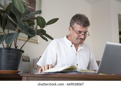 middle aged man working at this computer at his home office