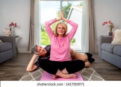 Middle aged married couple practicing Yoga in home living room, together, loving, caring, healthy relationship