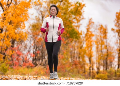 Middle aged mature Asian woman running healthy lifestyle Chinese lady jogging in fall park in her 50s. Middle age runner outdoor living in autumn city forest happy on weight loss fitness program.