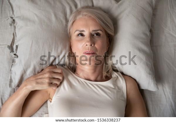 Reife Frau im mittleren Alter, die wach im Bett liegt und nach oben zu versuchen zu schlafen, unglücklich alte Senior Lady fühlen sich gestört leiden unter Schlaflosigkeit Konzept unangenehme schlechte Matratze, Draufsicht
