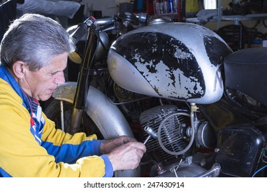a middle aged mechanic is repairing the engine of a classic motorbike in process of restoration at his workshop - focus on the man face