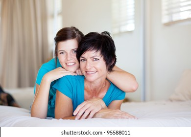 middle aged mother and teenager daughter relaxing on bed