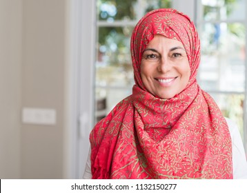 Middle aged muslim woman wearing hijab with a happy face standing and smiling with a confident smile showing teeth