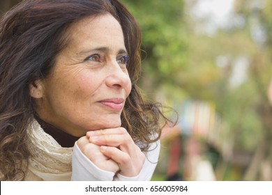 Middle aged nice lady with optimistic look resting face on her hands in the park. Visionary woman, entrepreneur imagination, pensive, freedom, retirement planning concepts