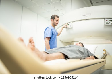 Middle aged patient with cancer and nurse during MRI in hospital lab. Man ins his 40s with doctor in clinic during medical examination. People and disease prevention with magnetic resonance imaging.
