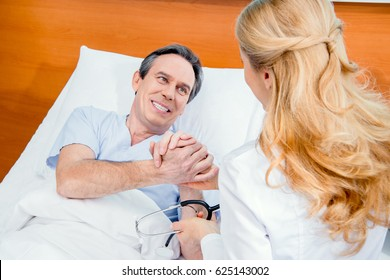 middle aged patient lying on bed and doctor holding his hands in hospital