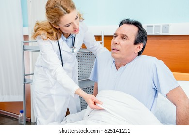 middle aged patient with pain sitting on bed, doctor helping him in hospital