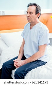 middle aged patient sitting on bed in chamber in hospital