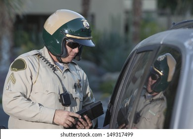 Middle aged policeman with clipboard standing by car