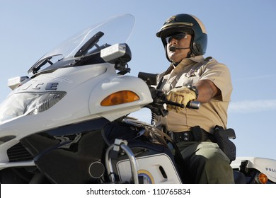 Middle aged policeman riding motorbike from below