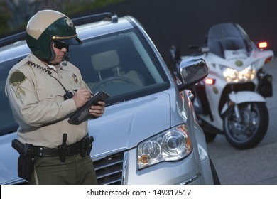 Middle aged policeman writing ticket while standing in front of car