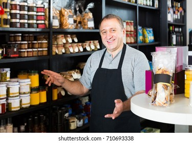 Middle aged positive salesman working in delicatessen section of ordinary grocery
