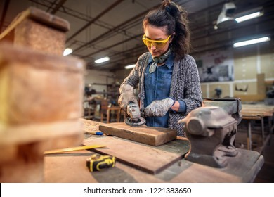 Middle aged professional female carpenter working with sandpaper in her workshop.