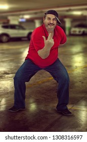 Middle aged rapper in red polo t-shirt and jeans performs in the underground parking lot.