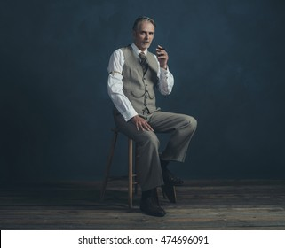 Middle aged retro 1920s man wearing suit with cigar sitting on wooden stool. Empty room. Vintage wooden floor.