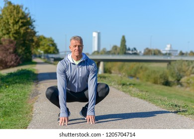 Middle aged runner sitting in a squat with his hands to the ground