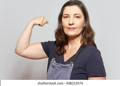 Middle aged and self-confident woman in dungarees flexing her biceps muscles, white background