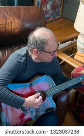 middle aged senior man playing acoustic guitar