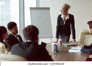 Middle aged serious boss talk to subordinates at meeting in boardroom, strict businesswoman scold employees or workers at briefing in office, successful female director speak on plans and strategies