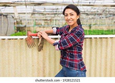 Middle aged smiling woman worker standing with rake and gardening gloves near fence at greenhouse farm
