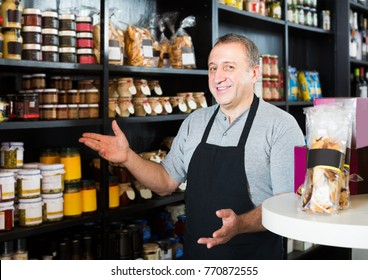 Middle aged spanish salesman working in delicatessen section of ordinary grocery