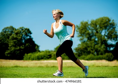 Middle aged sports woman running on grass field.