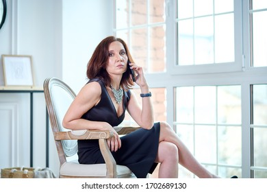 a middle aged stylish and defiant woman in a black dress has stayed at home because of the pandemic and is sitting in front of the large window of the house in a chair and talking on the phone