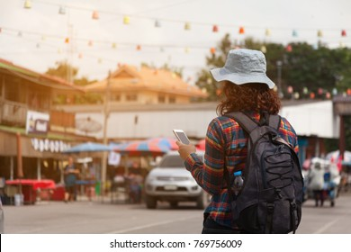Middle aged surfer girl Wear a hat and backpack. Walking tourism in Thailand, traveling much culture and local traditions concept.