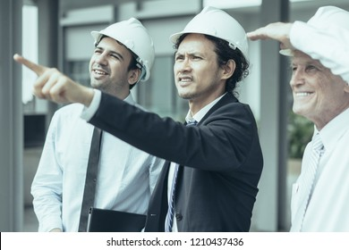 Middle aged tensed man in helmet and suit pointing at neighboring buildings to content partners. Construction manager showing site to two investors. Meeting and construction concept