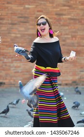 Middle aged Thai lady in colourful northern Thai style costume play with birds in tourist place in Chiang Mai Thailand with warm sun ray - woman portrait outdoor beautiful local environment concept
