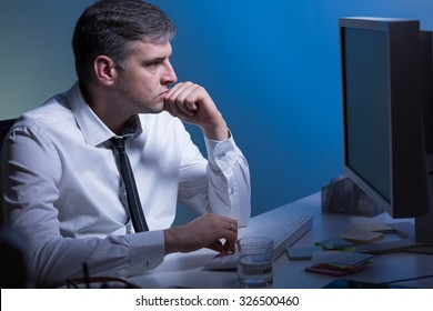 Middle aged thoughtful man working on computer