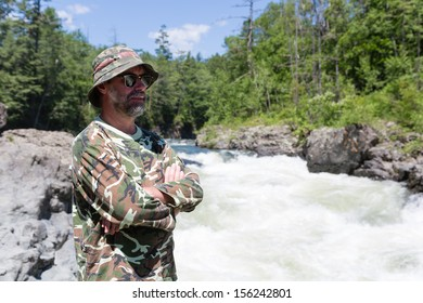 Middle aged traveler looking over the river with rapid flow.