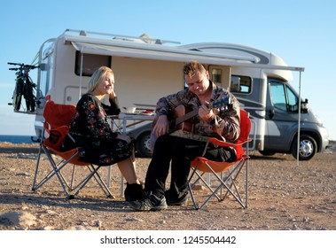 Middle aged travelers couple sitting on folding chairs take break during long trip by recreational vehicle motor home trailer. People in love having romantic date husband play guitar to loving wife