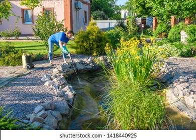 middle aged white woman cleans fish pond with high-pressure wash from sludge.