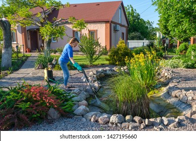 middle aged white woman cleans artificial pond with high-pressure wash from sludge. Spring and summer pond care work