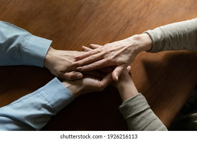 Middle aged wife holds hands of beloved mature husband. Elderly married couple of pensioners gives comfort, expresses trust, support and care. Close up of stack of arms with wedding ring. Hope concept