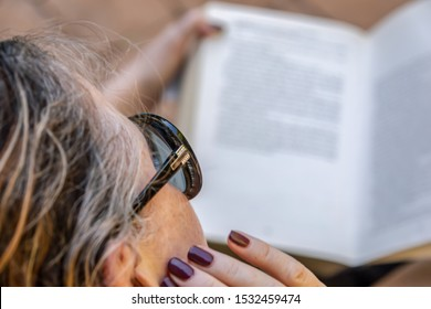 middle aged woman absorbed in the book reading exercise.