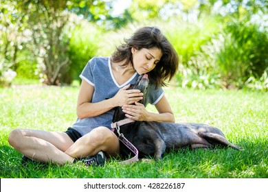 Middle aged woman affectionately holding her pet labrador retriever dog with dog licking her face at the park