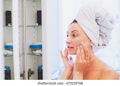 middle aged woman applying moisturising cream on her face after shower in bathroom in front of the mirror, skin care concept